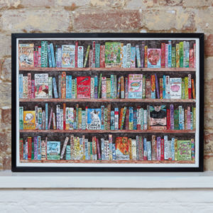 Picture of framed authorful puns print on white shelf against brick wall