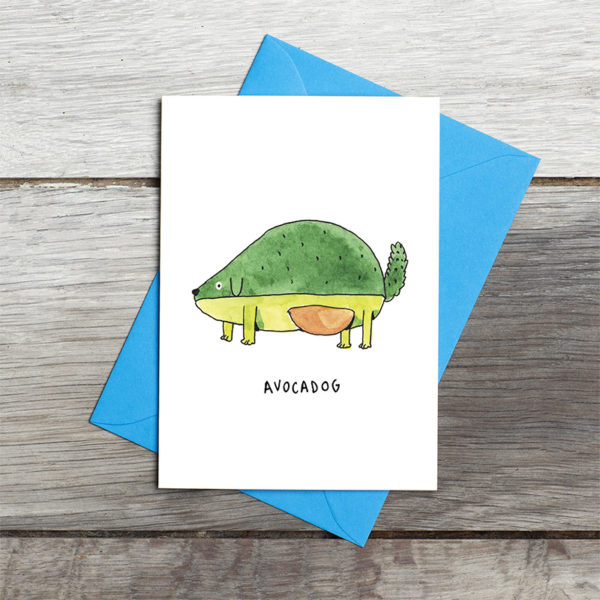 Grey wooden background. A blue envelope with the card lying on top. A green avocado drawn as a dog is on top. He had the pit as his tummy and has lime green paws and small floppy ears. The words 'Avocadog' are below.
