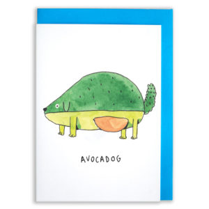 A card with a blue envelope tucked inside. An avocado, but as a dog. The tip of the avocado is his nose. The middle of the avocado has the pit as his tummy and he has green arms and paws. He also has a fluffy green tail.