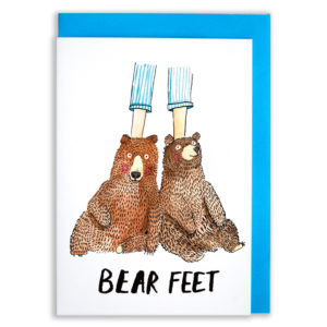A card with a blue envelope tucked inside. Two bears - but as feet! the bears are at the bottom of two legs wearing blue and white striped pyjamas. The bears look quite content and are just chilling out. Text below reads 'bear feet'.