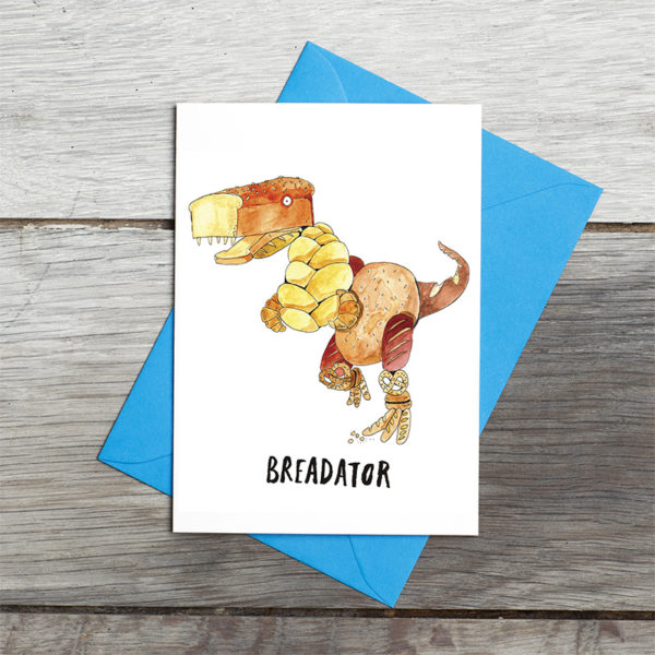 Grey wooden background. A blue envelope with the card lying on top. A dinosaur made of bread.Croissants for arms, pretzels for knees, baguettes for feet, a large tin loaf for a head, a large seeded loaf for a body. Text reads 'Breadator'.