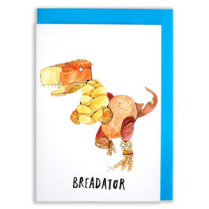 A card with a blue envelope tucked inside. A dinosaur made of bread.Croissants for arms, pretzels for knees, baguettes for feet, a large tin loaf for a head, a large seeded loaf for a body. Text reads 'Breadator'.