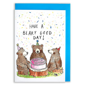 A card with a blue envelope tucked inside. Three bears wearing party hats are sat on grass around a birthday cake. There is colourful confetti falling. The text reads 'Have A Beary Good Day'