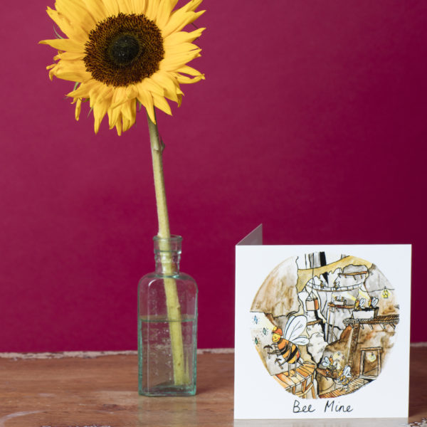 The bee mine card is on a table next to a sunflower.