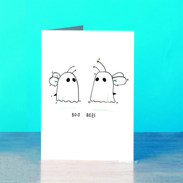 A blue background and a grey wooden table. On the table is a card. Two bees wearing sheets. You can tell they are bees and not ghosts due to their antenna, wings, and stings poking out of the sheets! Text below reads 'boo bees'.