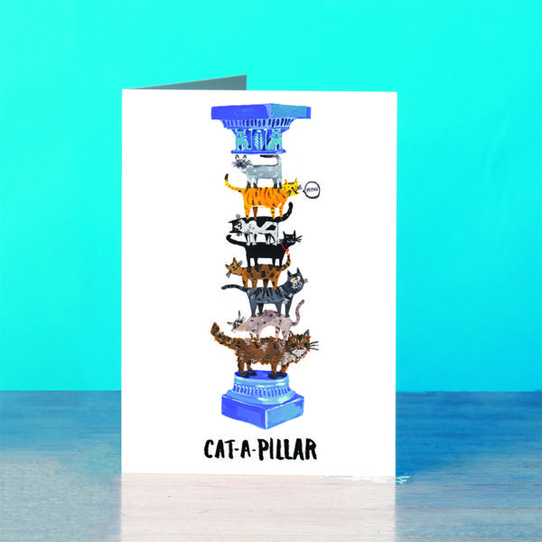 A blue background and a grey wooden table. On the table is a card. A pillar with a blue ornate decoration and the top and bottom. The middle of the column is made of various cats of all shapes and colours, one ginger cat is saying 'mow'.. The text reads 'Cat-a-pillar'.