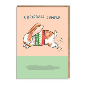 Top half of card is peach, bottom is green. A white and ginger rabbit is wearing a Christmas jumper and hopping across the card. Text reads: Christmas Jumper.