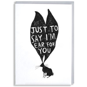 A black silhouette of a rabbit with very large ears. Inside the ears in white it says 'Just to say i'm ear for you'.