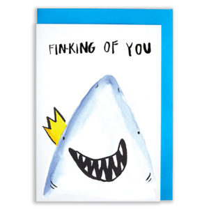A card with a blue envelope tucked inside. A close up of a shark's face smiling wide and showing teeth. The Shark is wearing a gold crown. Text reads Fin-King Of You'