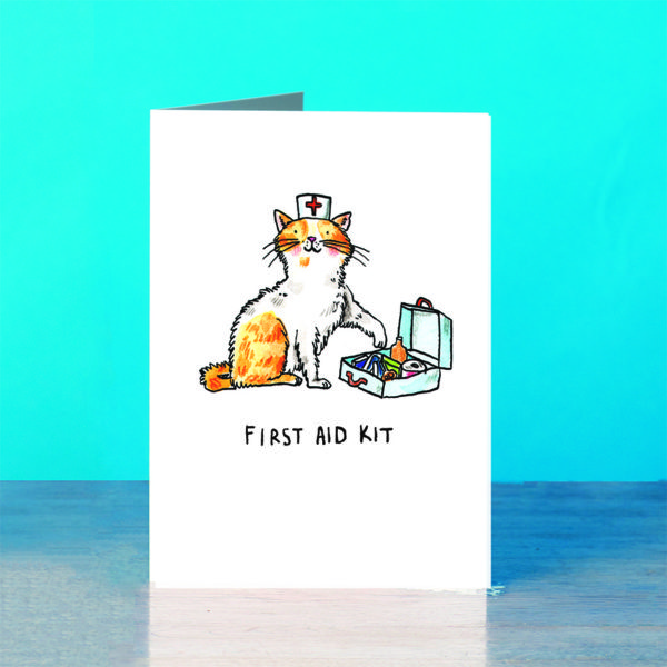 A blue background and a grey wooden table. On the table is a card. A ginger and white kitten with a white nurses hat with a red cross on is holding a paw out to a blue first aid kit filled with plasters and medicine. Text below reads 'First Aid Kit'.