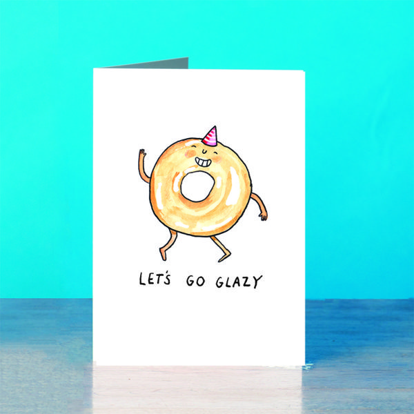 A blue background and a grey wooden table. On the table is a card. A glazed doughnut with a grin and a little hand waving. The doughnut is wearing a pink and white striper party hat. Text below reads 'Let's Go Glazy'.
