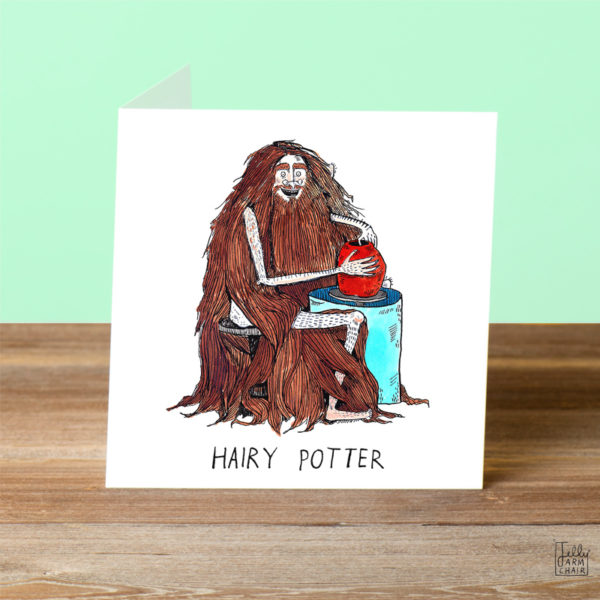 A bespectacled man with very very long brown hair and no clothes is sat at a blue pottery wheel making a red vase. Text: 'Hairy Potter'.