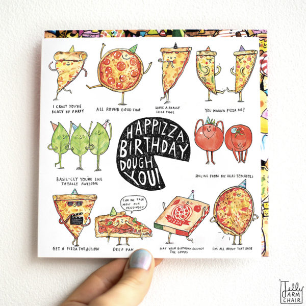 A card is being held against a white wall. A black pizza in the centre with text that reads 'Happizza Birthday Dough You''. This is surrounded by ten pizza puns.