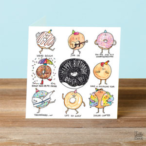 A blue background and a wooden table. On the table is a card. A black donut in the centre with text that reads 'Happy Birthday Dough You'. This is surrounded by eight donut puns.