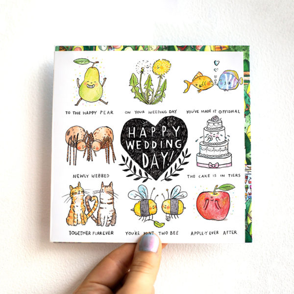 A card is being held against a white wall. A black heart in the centre with text that reads 'Happy Wedding Day'. This is surrounded by eight wedding puns.