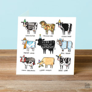 A blue background and a wooden table. On the table is a card. A black cow in the centre with text that reads 'Herd It's Your Birthday'. This is surrounded by eight cow puns.
