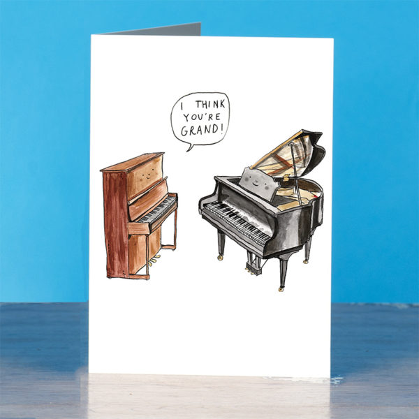 A brown upright piano is looking at a black grand piano, both are smiling. The upright is saying 'I think you're grand!'.