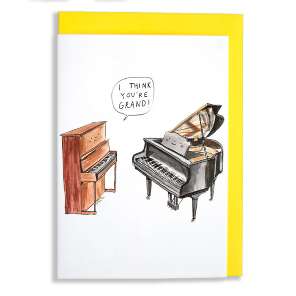 Yellow envelope with card. A brown upright piano is looking at a black grand piano, both are smiling. The upright is saying 'I think you're grand!'.