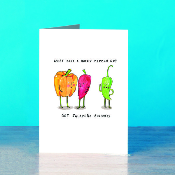 A blue background and a grey wooden table. On the table is a card. Writing at the top says 'What does a nosey pepper-' and below 'Get Jalapeno business' With an orange pepper talking to a red chilli and a green chilli is eavesdropping.