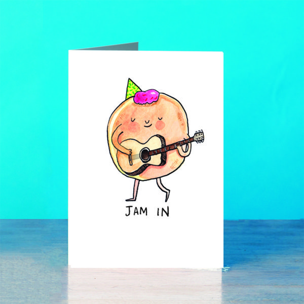 A blue background and a grey wooden table. On the table is a card. A round doughnut with pink jam for hair and a green party hat. The doughnut is smiling and holding a guitar. Text below reads 'Jam In'.