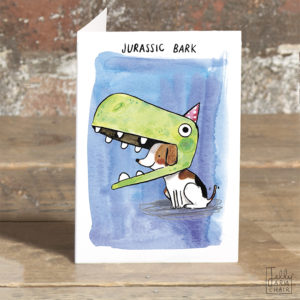 A card stood on a table. Small jack russell wearing a huge dinosaur costume hat, with a little red party hat on top. Text above reads 'Jurassic Bark'.