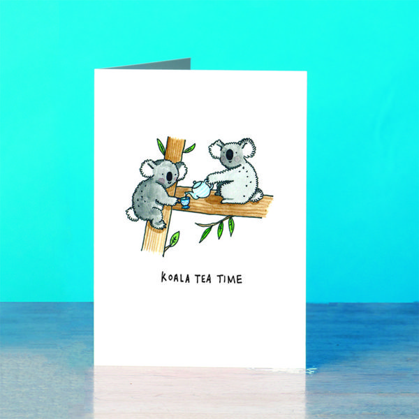 A blue background and a grey wooden table. On the table is a card.Two koalas in a tree having a cup of tea. One koala has a blue and white striped teapot and is pouring some tea into the other koalas blue and white dotty cup. Both are smily and fluffy and are having fun.