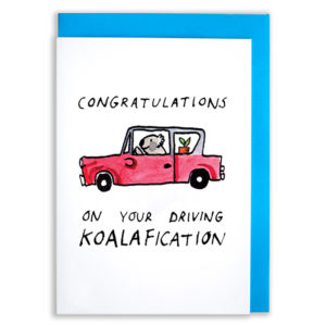 A card with a blue envelope tucked inside. A kola is driving a small red car. The text reads 'Congratulations on your driving koalafication'