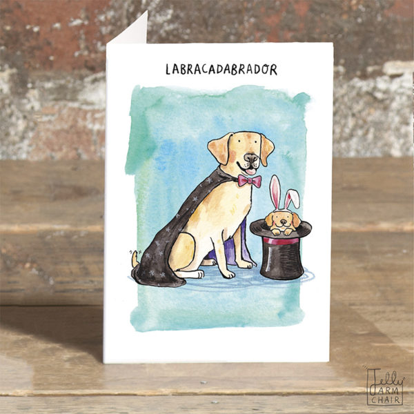 A card stood on a table. A Labrador in a magicians cape and pink bowtie, and a puppy in a top hat wearing bunny ears. Text above reads 'Labracadabrador'.