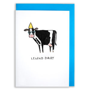 A card with a blue envelope tucked inside. A black and white cow whose markings look like a tuxedo! The cow has a spodge the shape of a tie, is wearing sun glasses and has a yellow party hat on. Text below reads 'Legend Dairy'.
