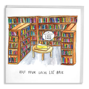 A library filled with colourful books, on a table is a brie which is saying 'I'm actually a hard cheese'. Text: 'Visit your local lie brie'.