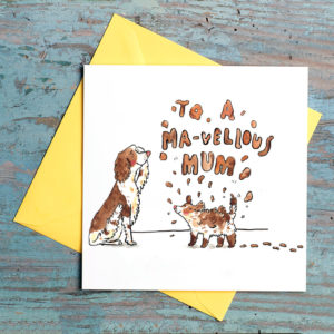 A brown and cream spaniel has a paw to her brow and a puppy is shaking mud everywhere. In the mud it says 'To a ma-vellous mum'.