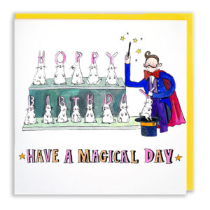 A yellow envelope with the card. A stage magician is holding a wand while white rabbits spell 'Happy birthday' with their ears. Text below reads 'Have a magical day'.