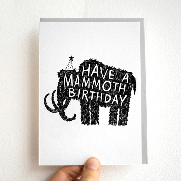 A black silhouette of a mammoth wearing a party hat. Inside the mammoth is white writing it says 'Have a mammoth birthday'
