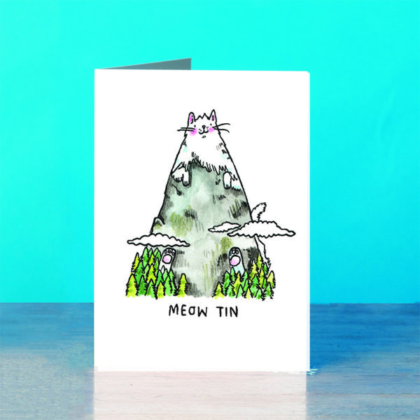 A blue background and a grey wooden table. A mountain peak rising above a forest and the clouds, with some white and pink paws poking out! The snow is a cat! A grey and white cat who is a mountain. The cat has pink rosy cheeks an a little smile. Text below reads 'Meow Tin'.