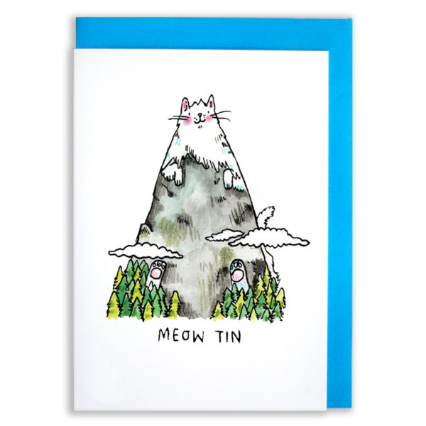 A card with a blue envelope tucked inside. A mountain peak rising above a forest and the clouds, with some white and pink paws poking out! The snow is a cat! A grey and white cat who is a mountain. The cat has pink rosy cheeks an a little smile. Text below reads 'Meow Tin'.