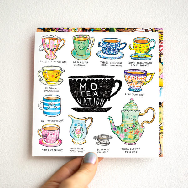 A card is being held against a white wall. A black tea cup in the centre with text that reads 'Mo-Tea_Vation'. This is surrounded by eleven tea puns.