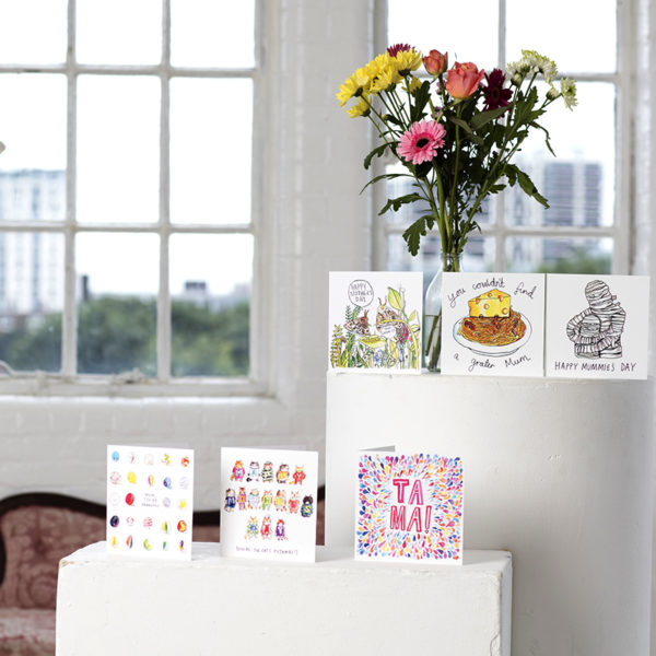A bouquet of flowers and three cards on a white table. On a lower white table are three more cards.