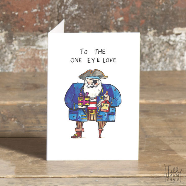 A pirate in a blue coat with a wooden leg an deye patch. He is holding a mini treasure chest tied with a bow and a bottle of rum. Text: To the one eye love'.