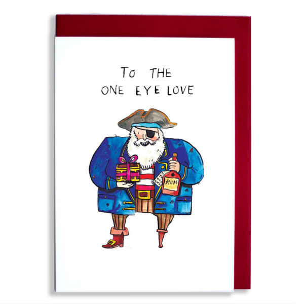 Red envelope with card. A pirate in a blue coat with a wooden leg an deye patch. He is holding a mini treasure chest tied with a bow and a bottle of rum. Text: To the one eye love'.