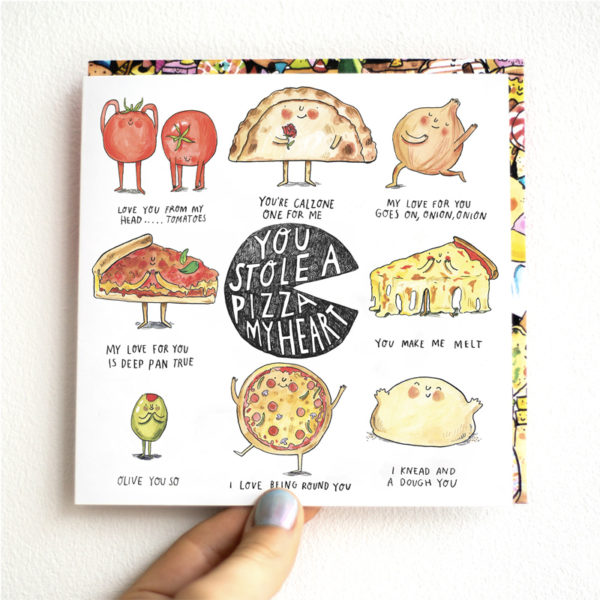 A card is being held against a white wall. A pizza in the centre with text that reads 'You Stole A Pizza My Heart'. This is surrounded by eight pizza puns.