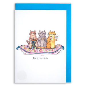A card with a blue envelope tucked inside. Three cats, one brown, one grey, one ginger, all sat on a paisley and flower patterned cushion. The brown cat has a drum, the grey has a triangle (and a derpy tongue!) and the ginger has some maraccas! Text below reads 'Purr Cushion'.