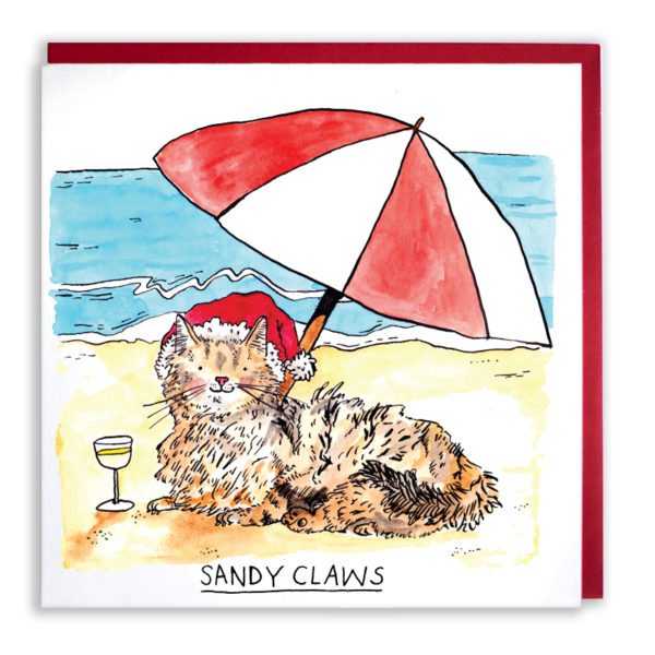 A fluffy ginger cat is lying on the beach with a glass of champagne, wearing a Santa hat, under a red and white beach umbrella. Text reads: 'Sandy Claws'.