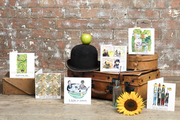 All of the art cards displayed amongst props such as an apple and bowler hat, a sunflower, a leather trunk, and a paintbrush and pot.