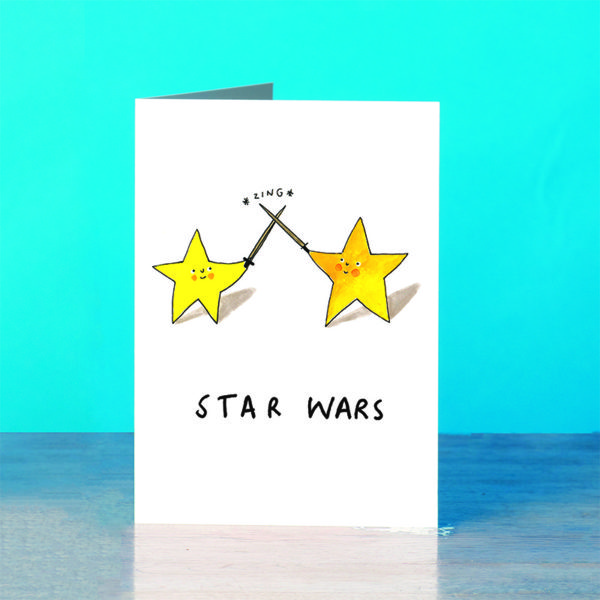 A blue background and a grey wooden table. Two stars are duelling, their swords are clashing and going *zing*. The stars have smiley faces and red cheeks. Text reads 'Star Wars'.
