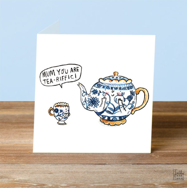 A blue and white smily teapot and a gold handle. Next to it is a little teacup of the same design. The teacup is saying 'Mum you are tea-riffic!'.