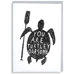 A black silhouette of a turtle holding an oar in its fin. On the shell in white it says 'You are turtley oarsome'.