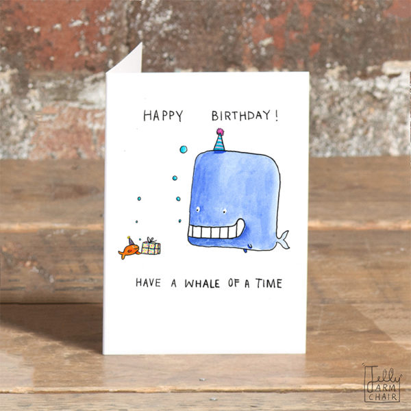 Text at the top says 'Happy birthday!' Below this is a whale with a big grin and a little orange fish with a present. Below this it says 'Have a whale of a time'.