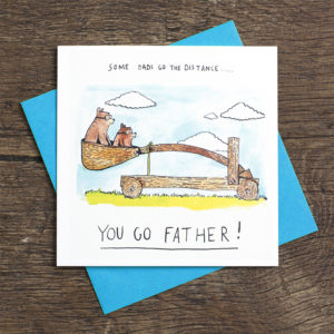 Two bears, one big one small, are in a large wooden catapult. Text above reads 'Some dads go the distance...' Text below reads 'Yo go father!'.
