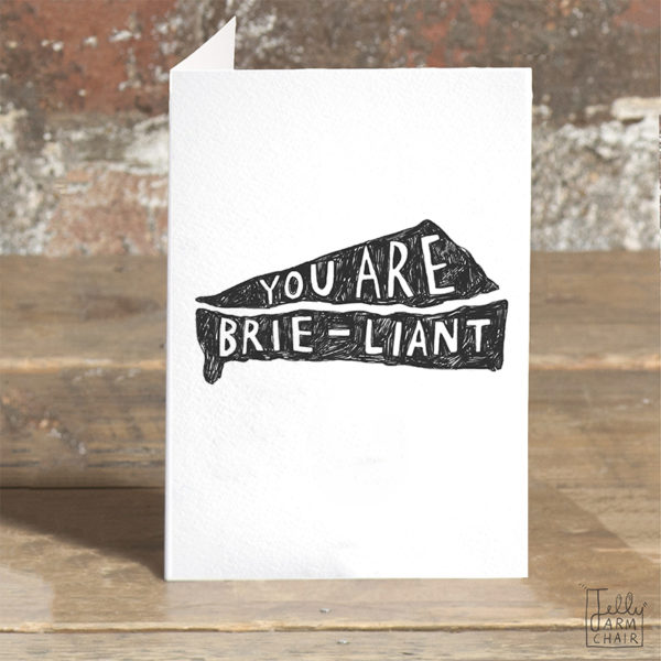 A card on a wooden table. On the card a black silhouette of a brie, inside in white it says 'You are brie-liant'.