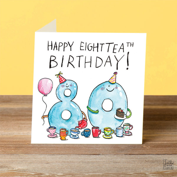 A card on a wooden table. Text at the top reads 'Happy Eighttea-th birthday!'. A blue * an d) are smiling and having a tea party with balloons and birthday cake.